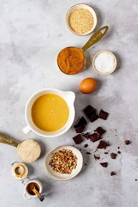 Top view of ingredients for making paleo pumpkin cookies on a grey background