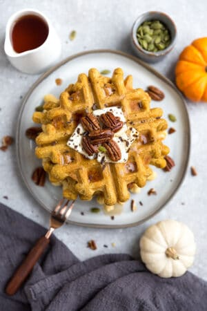 Top view of a stack of thick and fluffy Keto Pumpkin Waffles on a white plate with a fork and knife