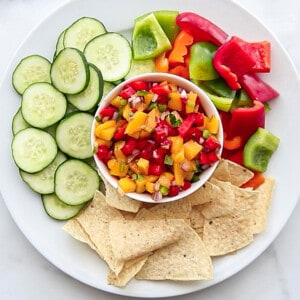 Top view of a bowl of fresh mango salsa served with sliced cucumbers, bell peppers and chips