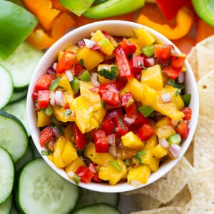 Top shot of a serving of fresh mango salsa in a white bowl with sliced cucumbers, bell peppers and tortilla chips