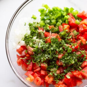 A clear mixing bowl filled with ingredients to make the tomato salsa