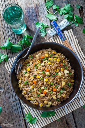 Top view of Chinese fried rice in a black bowl with a spoon