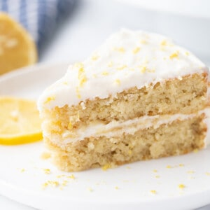 Landscape side shot of a slice of gluten free lemon cake on a white plate