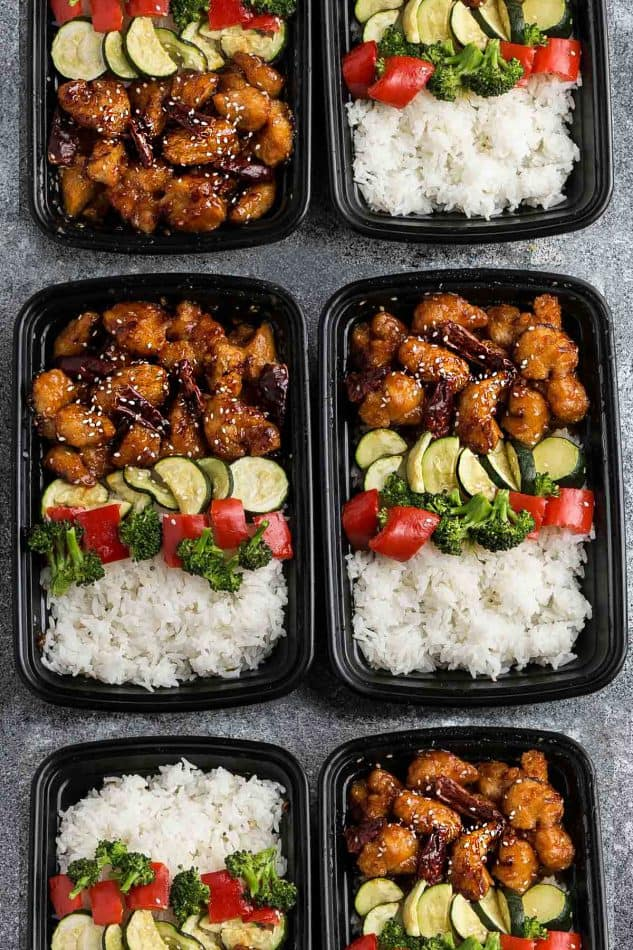 meal prep containers filled with General Tso's Chicken, white rice and steamed vegetables