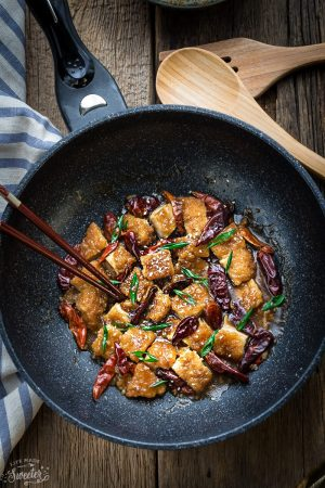 General Tso's Chicken in a black skillet with dark brown chopsticks.
