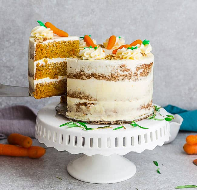 Gluten Free Carrot Cake on a white cake stand with a slice being lifted out