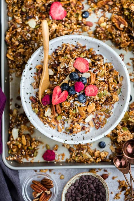 Top view of paleo granola in a white bowl with a gold spoon on a baking sheet