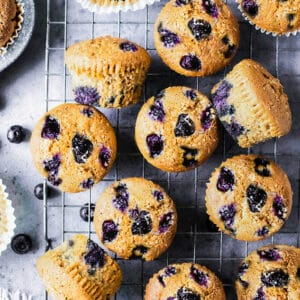 Top view of scattered keto blueberry muffins on a wire rack on a grey background with fresh blueberries