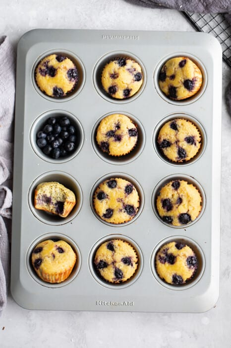 Overhead view of Lemon Blueberry Muffins in a tin with blueberries in one cup