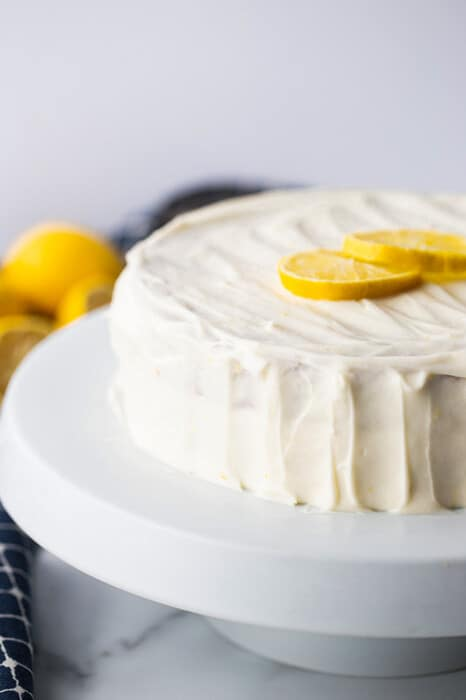 Side shot of a frosted layered healthy lemon cake on a white plate