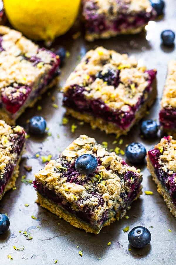 Front view of paleo blueberry crumble bars topped with fresh blueberries.