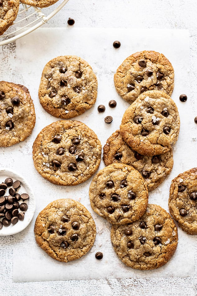 Overhead image of paleo chocolate chip cookies on white background with chocolate chips.