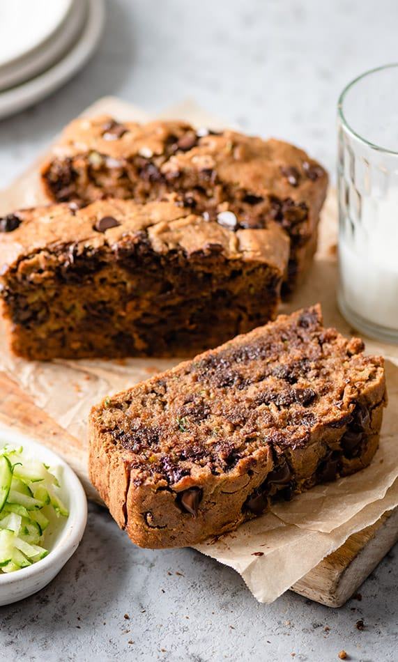 Front view of zucchini bread on parchment paper and wooden serving tray.