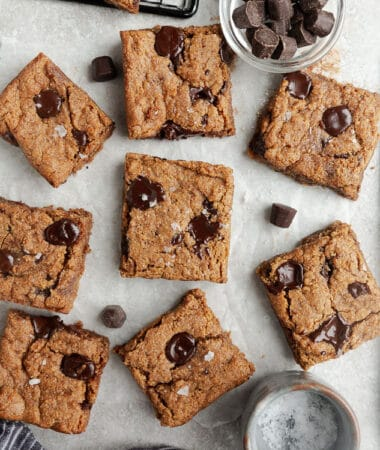Top view of 8 scattered paleo blondies chocolate chip cookie bars on a white background