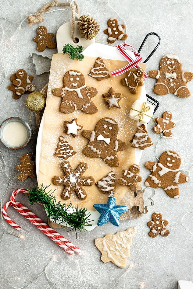 Top view of decorated vegan gingerbread cookies on a wooden cutting board on a grey background with cookie cutters