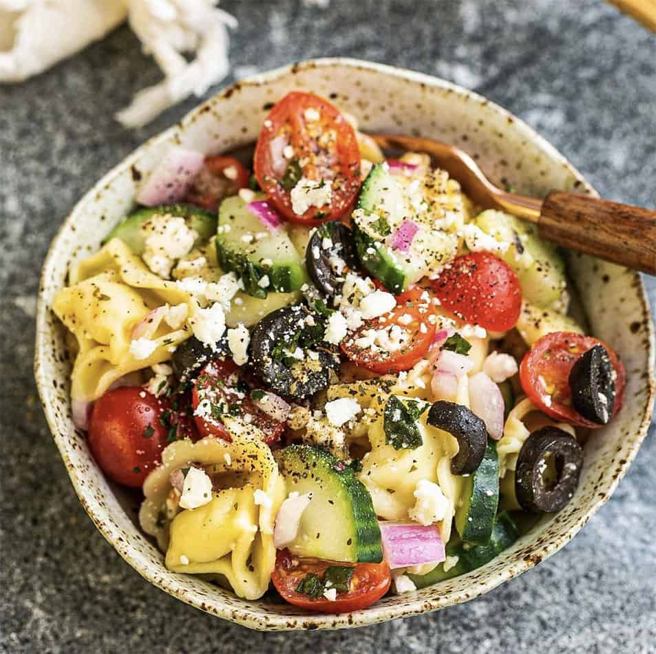 A ceramic speckled bowl with gluten free tortellini pasta salad with a wooden fork