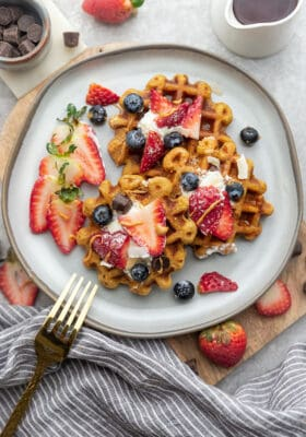 Top view of four gluten free waffles on a grey plate with a gold fork