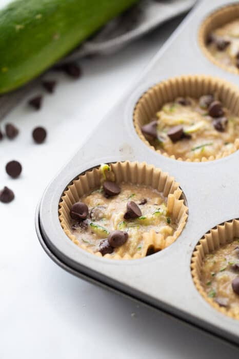 Close-up view of zucchini muffin batter in a muffin tin