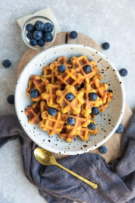 Top view of paleo waffle cereal in a white bowl with blueberries