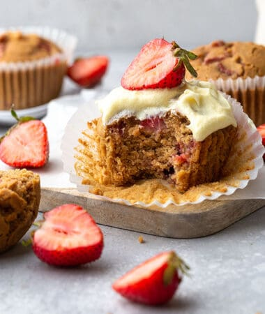 Side view of one gluten-free strawberry muffin topped with whipped coconut cream with a missing bite on a grey background