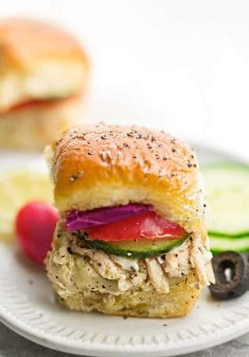 Greek Chicken Sliders - perfect easy appetizers for parties, game day and barbecues. Made with tender chicken, feta, gooey cheese and topped with cool and creamy Tzatziki sauce.