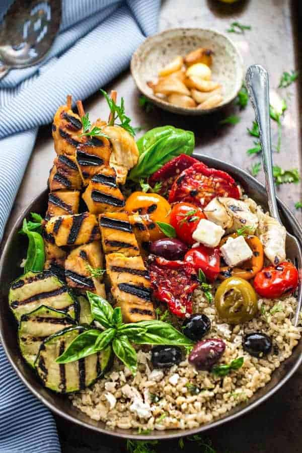 "Low Carb Chicken Souvlaki Bowls - the perfect healthy, low carb 30 minute dinner bursting with Mediterranean flavors. Best of all, it's full of fresh bright flavors with tender chicken, grilled vegetables, olives, feta on a bed of cauliflower ""rice""."