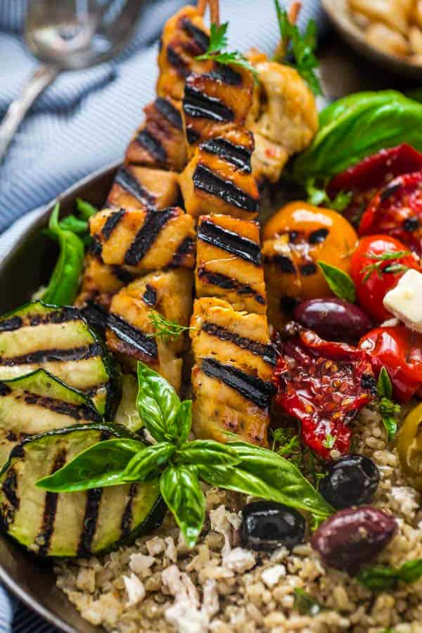 "Low Carb Greek Chicken Souvlaki Bowls - the perfect healthy, low carb 30 minute dinner bursting with Mediterranean flavors. Best of all, it's full of fresh bright flavors with tender chicken, grilled vegetables, olives, feta on a bed of cauliflower ""rice""."