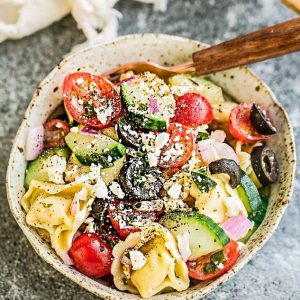Greek Tortellini Pasta Salad - the perfect Mediterranean inspired side dish to bring to summer potlucks, parties, Memorial Day / Fourth of July grillouts/barbecues. Best of all, it's so easy to make and easy to customize with your favorite toppings and homemade dressing. Perfect for Sunday meal prep and leftovers are delicious for school or work lunchboxes or lunchbowls.