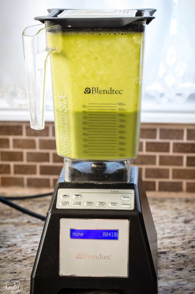 Side view of green smoothie in a blender