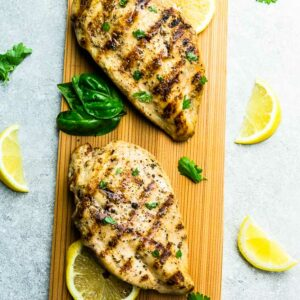 Top view of two grilled chicken breasts on a wooden cutting board on a grey background