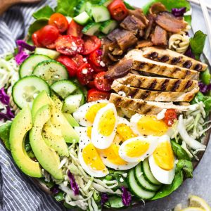 Top view of Cobb Salad with grilled chicken in a bowl on a grey background with lemon slices