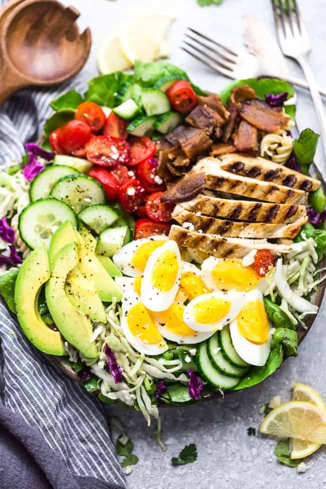 Top view of Cobb Salad with grilled chicken in a bowl on a grey background with forks, lemon slices