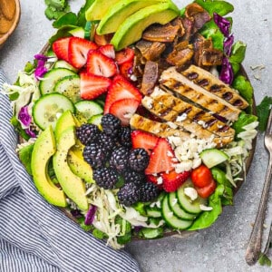 Top view of a loaded grilled chicken salad with berries in a bowl with two forks