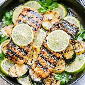 Top view of two Honey Lime Salmon fillets in a skillet with sliced zucchini and limes