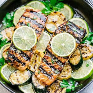 A Top View of Two Garlic Lime Salmon Fillets in a Skillet with Sliced Zucchini and Limes