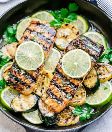 Top view of grilled salmon fillets in a cast iron pan with lime slices and zucchini