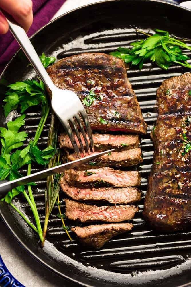 Perfectly grilled teak on grill top with fork and knife.