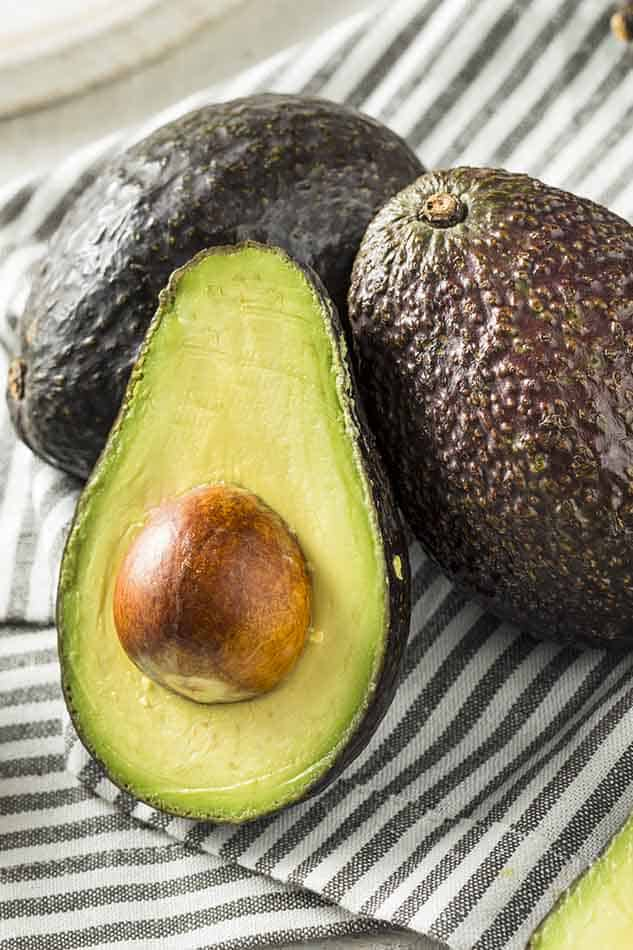 Front view of avocado on striped cloth.