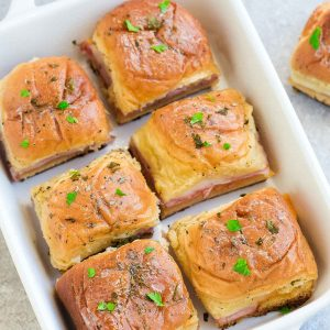 These Hot Oven Baked Ham and Cheese Slidersare the perfect game day snacks or appetizers. Best of all, they are a great way for using up any leftover ham from Thanksgiving, Christmas and Easter. Super easy to make with oven roasted ham, two cheeses and buttery garlic sauce over Hawaiian rolls.Great for feeding a crowd for a party or game day! #gameday #sliders #ham #cheese #swiss #cheddar #snacks #appetizer