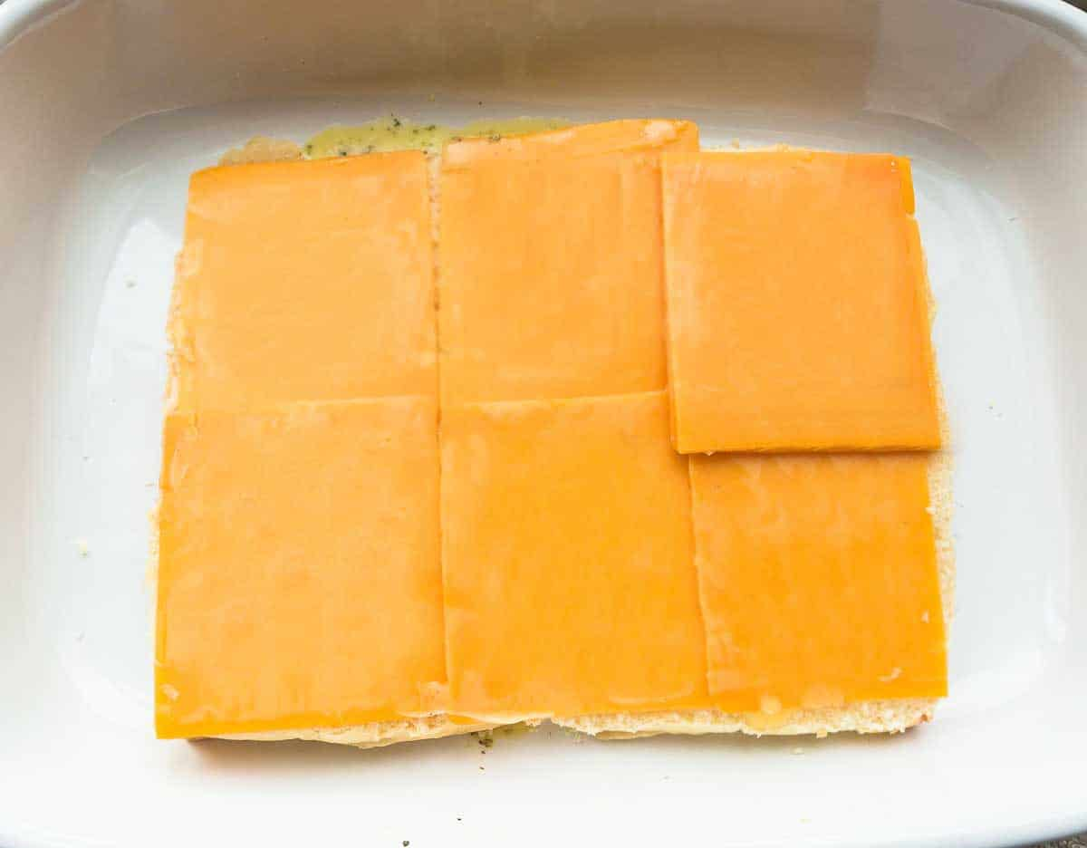The Bottom Halves of the Rolls Layered Up with Slices of Cheddar Cheese