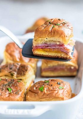 Spatula with a ham and cheese slider over a pan of buns