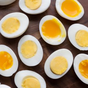 Top view of hard boiled and soft boiled eggs on a wooden cutting board