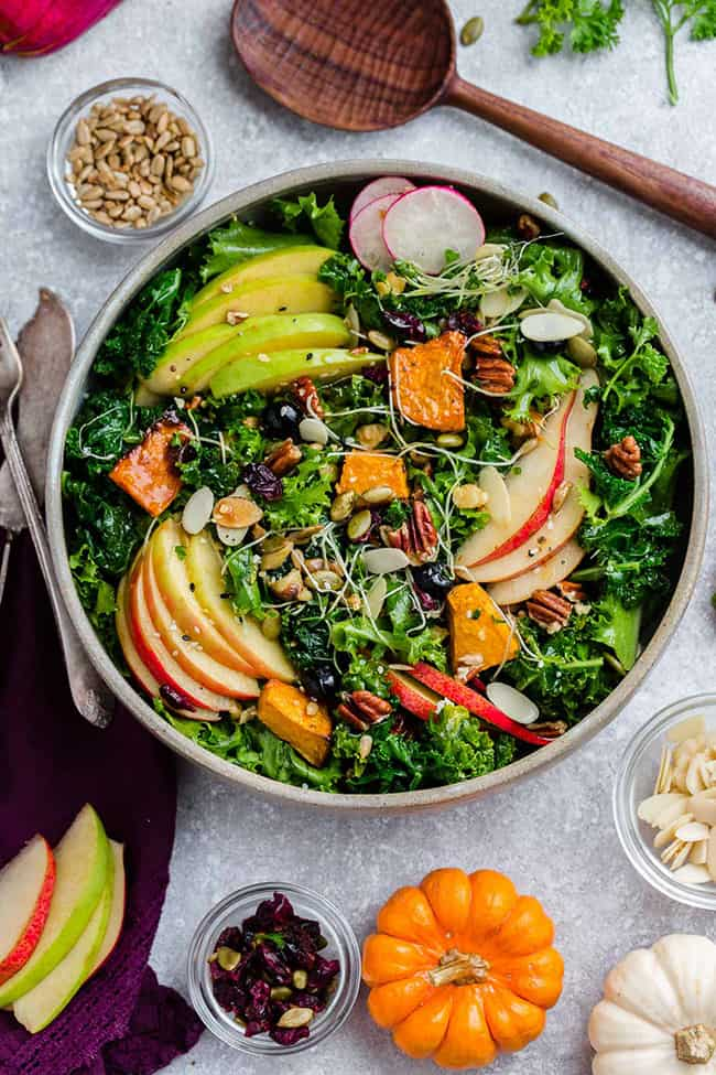 Top view of Fall Salad with Kale & roasted delicata squash in a bowl on a grey background