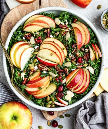 Top view of harvest kale salad with sliced apples in a white bowl