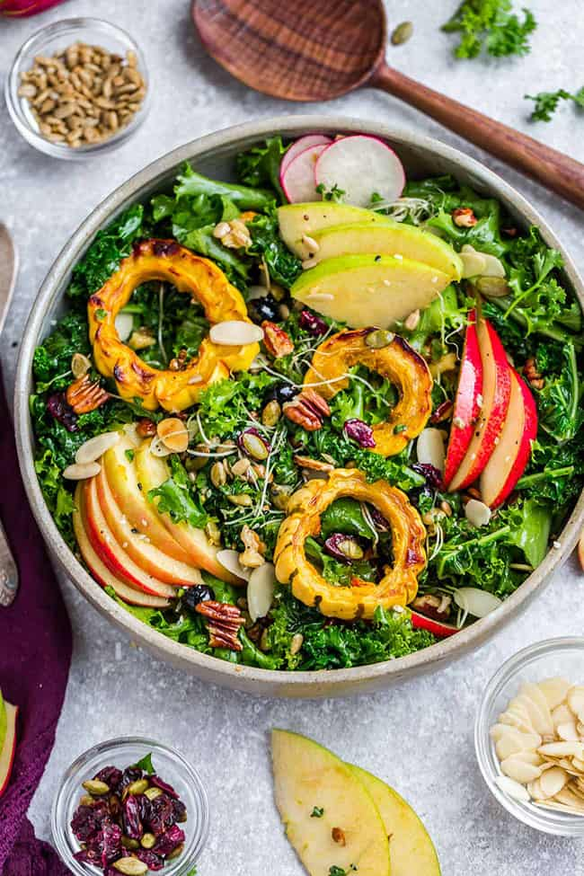 Harvest Kale Salad is full of hearty autumn vegetables, in season fruit drizzled with a healthy and simple apple cider vinaigrette. Made with kale, endive, chicken, crispy apples, pears, roasted pumpkin, cranberries and crunchy pecans. Gluten free, refined sugar free with paleo, low carb, keto & Whole 30 options.