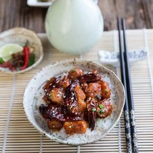 A bowl of General Tso's Chicken over white rice in a bowl next to chopsticks
