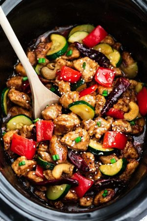 Healthier Kung Pao Chicken and wooden spoon in slow cooker.