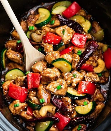 Close up of Slow Cooker Kung Pao Chicken with a wooden spoon in a crock pot