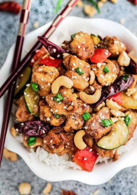 Kung Pao Chicken Stir Fry on a bed of white rice in a small white bowl with wooden chopsticks.