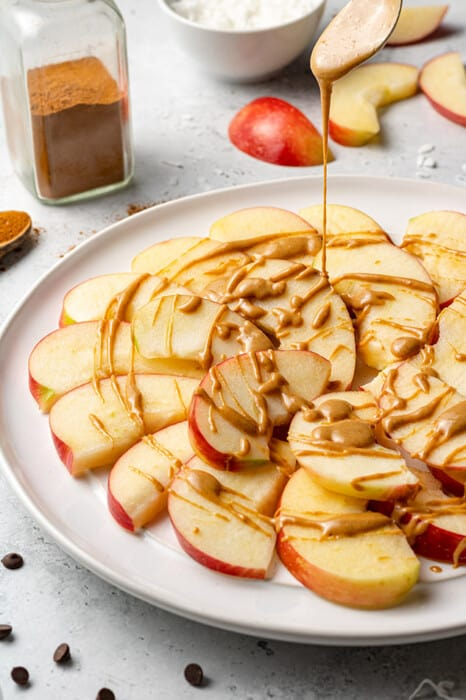 Nut butter being drizzled over apple slices on a plate
